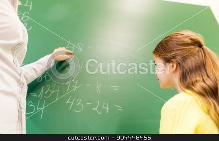 schoolgirl and teacher with task on chalk board stock photo, education, elementary school, learning, math and people concept - close up of little schoolgirl with teacher and task on chalk board at classroom by Syda Productions