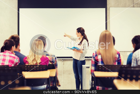 group of smiling students in classroom stock photo, education, high school, teamwork and people concept - smiling student girl with notebook standing and pointing finger in front of students in classroom by Syda Productions