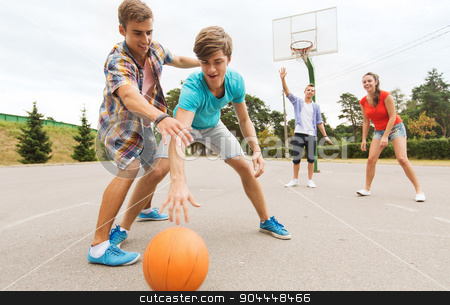 group of happy teenagers playing basketball stock photo, summer vacation, sport, games and friendship concept - group of happy teenagers playing basketball outdoors by Syda Productions
