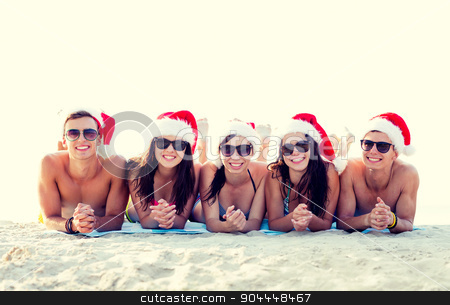 group of friends in santa helper hats on beach stock photo, friendship, happiness, summer vacation, holidays and people concept - group of friends in santa helper hats on beach by Syda Productions