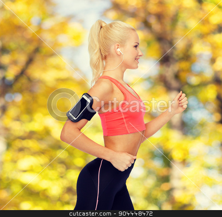 sporty woman running with smartphone and earphones stock photo, sport, exercise, technology, internet and healthcare - smiling sporty woman running and listening to music from smartphone by Syda Productions