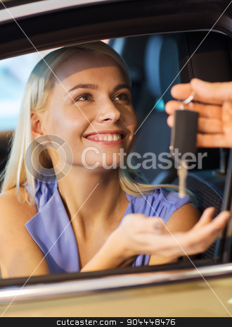 happy woman getting car key in auto show or salon stock photo, auto business, car sale, consumerism and people concept - happy woman taking car key from dealer in auto show or salon by Syda Productions
