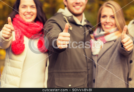 happy friends showing thumbs up in autumn park stock photo, friendship, gesture, season and people concept - close up of happy friends showing thumbs up in autumn park by Syda Productions