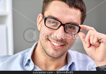 portrait of businessman in eyeglasses at office stock photo, business, people and work concept - portrait of smiling businessman in eyeglasses face in office by Syda Productions