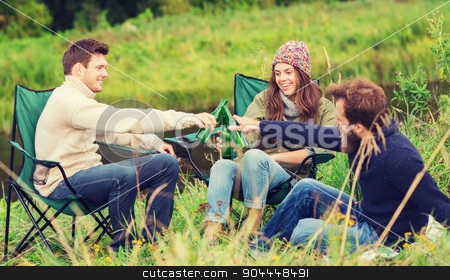 group of smiling tourists drinking beer in camping stock photo, adventure, travel, tourism, friendship and people concept - group of smiling tourists clinking beer bottles in camping by Syda Productions