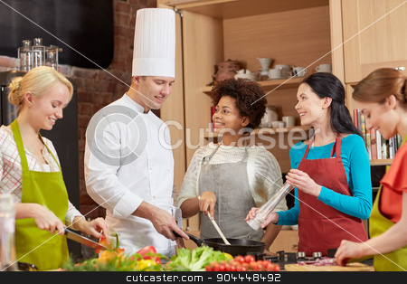 happy women and chef cook cooking in kitchen stock photo, cooking class, culinary, food and people concept - happy group of women and male chef cook cooking in kitchen by Syda Productions