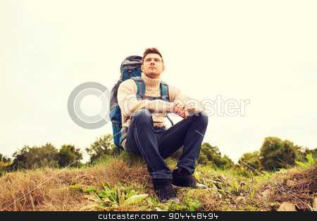 man with backpack hiking stock photo, adventure, travel, tourism, hike and people concept - man with backpack sitting on ground by Syda Productions