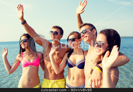 smiling friends in sunglasses on summer beach stock photo, friendship, sea, holidays, gesture and people concept - group of smiling friends wearing swimwear and sunglasses waving hands on beach by Syda Productions