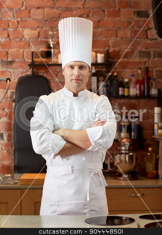 happy male chef cook in restaurant kitchen stock photo, cooking and people concept - happy male chef cook with crossed hands in restaurant kitchen by Syda Productions