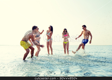 happy friends having fun on summer beach stock photo, friendship, sea, summer vacation, holidays and people concept - group of happy friends having fun on beach by Syda Productions