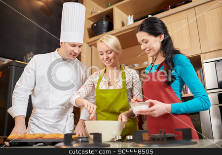 happy women and chef cook baking in kitchen stock photo, cooking class, culinary, bakery, food and people concept - happy group of women and male chef cook baking muffins in kitchen by Syda Productions