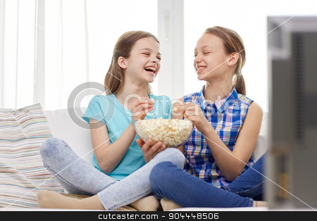 happy girls with popcorn watching tv at home stock photo, people, children, friends and friendship concept - two happy little girls watching tv, laughing and eating popcorn at home by Syda Productions