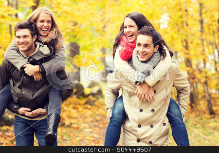 smiling friends having fun in autumn park stock photo, love, friendship, family and people concept - smiling friends having fun in autumn park by Syda Productions