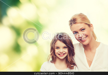 smiling mother and little girl stock photo, family, childhood, happiness, ecology and people - smiling mother and little girl over green background by Syda Productions