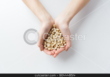 close up of woman hands holding peeled peanuts stock photo, healthy eating, dieting, vegetarian food and people concept - close up of woman hands holding peeled peanuts at home by Syda Productions