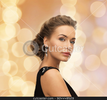 beautiful woman in evening dress wearing earrings stock photo, people, holidays, christmas and glamour concept - beautiful woman in evening dress wearing earrings over beige lights background by Syda Productions