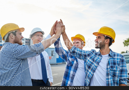 close up of builders in hardhats making high five stock photo, business, building, partnership, gesture and people concept - close up of smiling builders and architect in hardhats making high five outdoors by Syda Productions