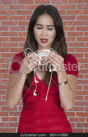 Woman with tangled headphones stock photo, Beautiful woman with tangled headphones in a twisted mess by Robert Byron