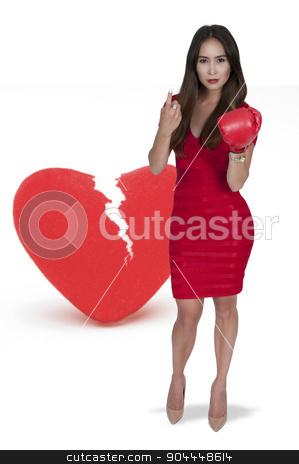 Broken Heart stock photo, Beautiful woman in wearing a boxing glove in front of a broken heart - heartbreaker by Robert Byron
