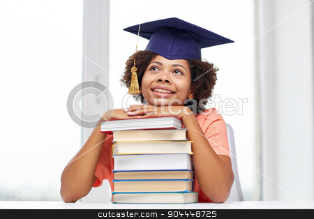 happy african bachelor girl with books at home stock photo, education, school, knowledge and people concept - happy smiling african american student girl in bachelor cap with books sitting at table and dreaming at home by Syda Productions