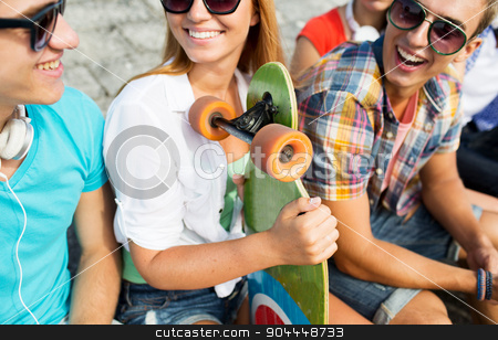 close up of happy friends with longboard on street stock photo, people, leisure, communication and sport concept - close up of happy teenage friends with longboard talking on city street by Syda Productions