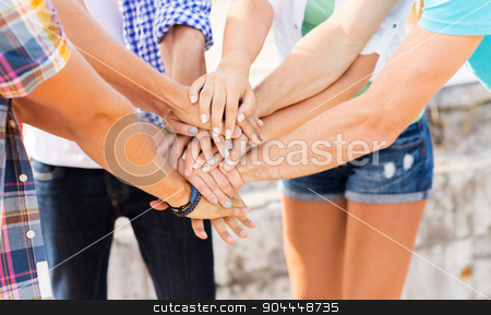 close up of friends hands on top stock photo, success, people, teamwork and gesture concept - cclose up of friends hands on top of each other outdoors by Syda Productions