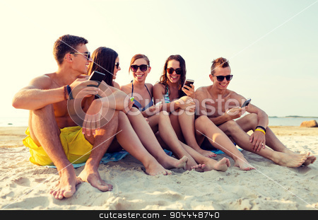 friends with smartphones on beach stock photo, friendship, leisure, summer, technology and people concept - friends with smartphones sitting on sandy beach by Syda Productions