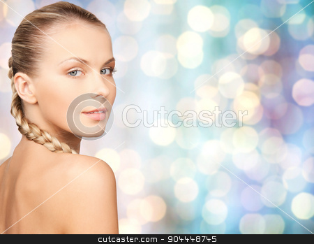 beautiful young woman touching her face stock photo, beauty, people and body care concept - beautiful young woman with bare shoulders over blue holidays lights background by Syda Productions