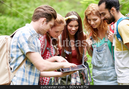 happy friends with backpacks and tablet pc hiking stock photo, technology, travel, tourism, hike and people concept - group of smiling friends walking with backpacks and tablet pc computer looking for location in woods by Syda Productions
