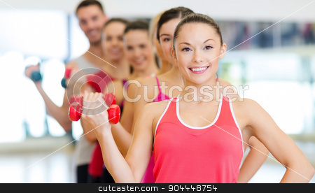 group of smiling people with dumbbells in the gym stock photo, fitness, sport, training, gym and lifestyle concept - group of smiling people lifting dumbbells in the gym by Syda Productions
