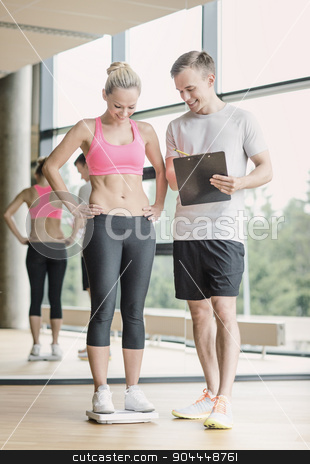 smiling man and woman with scales in gym stock photo, sport, fitness, lifestyle and people concept - smiling man and woman with scales and clipboard in gym by Syda Productions