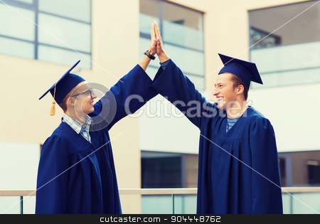 smiling students in mortarboards stock photo, education, graduation and people concept - smiling students in mortarboards and gowns making high five gesture outdoors by Syda Productions