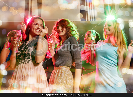 smiling friends with glasses of champagne in club stock photo, party, holidays, celebration, nightlife and people concept - smiling friends with glasses of champagne dancing in club by Syda Productions