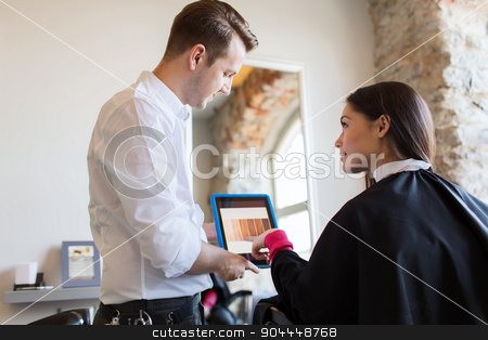 happy woman and stylist with tablet pc at salon stock photo, beauty, technology and people concept - happy young woman and stylist with tablet pc computer choosing hair color at salon by Syda Productions