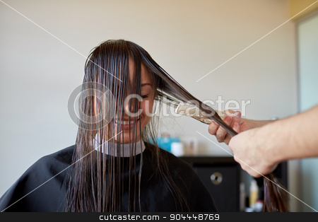 happy woman with stylist cutting hair at salon stock photo, beauty, hairstyle and people concept - happy young woman and hairdresser hands with scissors and comb cutting hair tips at salon by Syda Productions