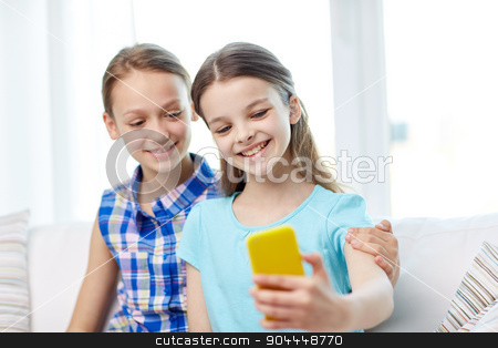 happy girls with smartphone taking selfie at home stock photo, people, children, technology, friends and friendship concept - happy little girls sitting on sofa and taking selfie with smartphone and hugging at home by Syda Productions