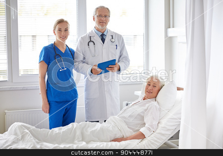 doctor and nurse visiting senior woman at hospital stock photo, medicine, age, health care and people concept - doctor and nurse with tablet pc computer visiting senior patient woman at hospital ward by Syda Productions