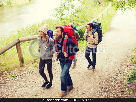 group of smiling friends with backpacks hiking stock photo, adventure, travel, tourism, hike and people concept - group of smiling friends walking with backpacks by Syda Productions