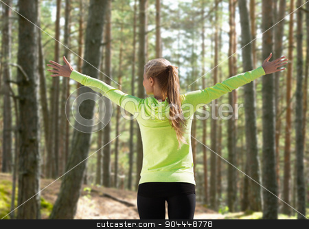 happy woman in sport clothes raising hands stock photo, fitness, sport, happiness and people concept - happy woman raising hands over woods background from back by Syda Productions