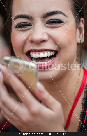 Girl in traditional Dirndl dress having fun while using her mobile phone at Oktoberfest stock photo, Girl in traditional Dirndl dress, Asian and German multi-racial, drinking beer and having fun while using her mobile phone at Oktoberfest by uleiber