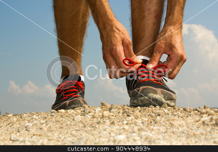 Runner tying shoelaces stock photo, Runner tying his shoelaces before training by Roland Valentin Raicu