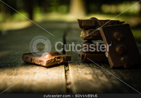 Chocolate on a wooden table stock photo, Chocolate pieces on a wooden table in park by Roland Valentin Raicu