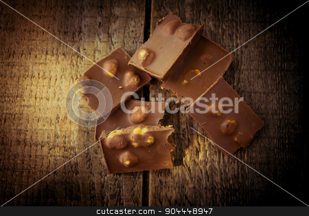 Chocolate on a wooden table stock photo, Chocolate pieces on a wooden table by Roland Valentin Raicu