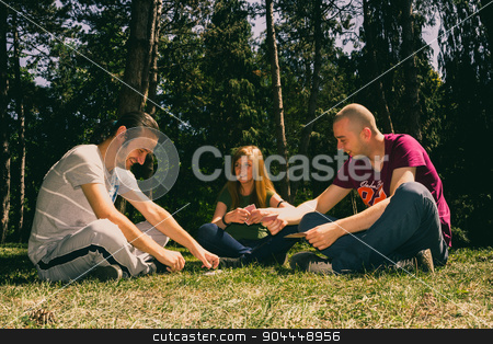 Three friends having fun stock photo, Three friends having fun by playing cards in the forest by Roland Valentin Raicu