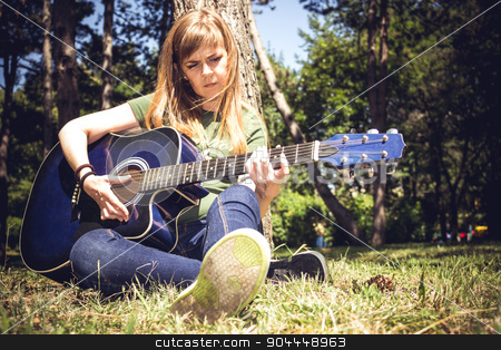 Guitar Player stock photo, Girl singing to a guitar surrounded by trees in a park by Roland Valentin Raicu