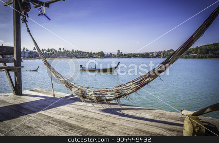Old hammock on wooden terrace stock photo, Old hammock on wooden terrace and seascape with boat by manusy