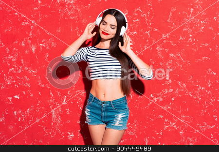 Creative concept of beautiful sexy girl stock photo, Colorful picture of beautiful slim young woman with long hair on red background. Girl with headphones smiling and listening to music with her eyes closed by Dmytro Sidelnikov