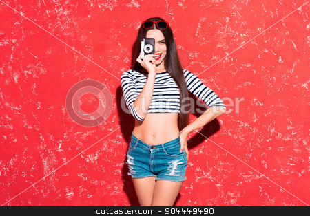 Creative concept of beautiful sexy girl stock photo, Colorful picture of beautiful slim young woman with long hair on red background. Girl looking at camera, smiling and holding old fashioned camera by Dmytro Sidelnikov
