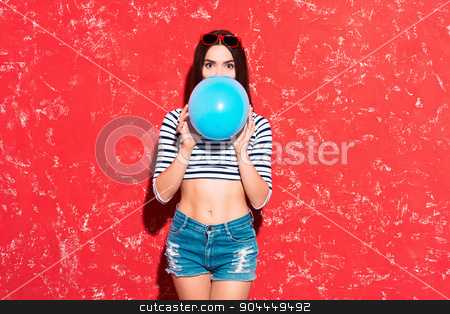 Creative concept of beautiful sexy girl stock photo, Colorful picture of beautiful slim young woman with long hair on red background. Girl looking at camera and inflating blue baloon by Dmytro Sidelnikov