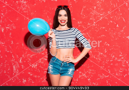 Creative concept of beautiful sexy girl stock photo, Colorful picture of beautiful slim young woman with long hair on red background. Girl looking at camera, smiling and holding blue baloon by Dmytro Sidelnikov